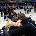 A supporter comforts a friend after invading the pitch of the Stade de France stadium at the end of the international friendly soccer match between France and Germany in Saint Denis, outside Paris, Friday, Nov. 13, 2015. Hundreds of people spilled onto the field of the Stade de France stadium after explosions were heard nearby. French President Francois Hollande says he is closing the country's borders and declaring a state of emergency after several dozen people were killed in a series of unprecedented terrorist attacks. (AP Photo/Christophe Ena)