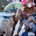 """Cuban migrants are reflected in the window of a nun's jeep, as they gather round for free breakfast items, near the immigration office in PeÒas Blancas, Costa Rica, Tuesday, Nov. 17, 2015. More than 1,000 Cuban migrants heading north to the United States tried to cross the border from Costa Rica into Nicaragua, causing tensions to soar between the neighbors as security forces sought to turn them back. Nicaragua's government responded furiously on Sunday with a statement saying that Costa Rica """"had deliberately and irresponsibly thrown, and continues to throw"""" the Cuban migrants into its territory, violating its national sovereignty. (AP Photo/Esteban Felix)"""