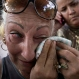 Nereida Sanchez Paz, 54, wipes away tears as she stands with others outside Ecuador's embassy expressing frustration at a new visa rule that now requires Cubans have a visa to visit the South American country, in Havana, Friday, Nov. 27, 2015. The lack of a visa requirement for Cubans made Ecuador a favored destination for those seeking to leave the island and make the overland route to the United States, where they can receive automatic legal residency. (AP Photo/Ramon Espinosa)