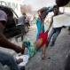 Protesters drag to safety a fellow demonstrator injured by a machete when he was attacked by a resident in a neighborhood known for its support of the ruling party, during a protest march against official preliminary election results, in Port-au-Prince, Haiti, Friday, Nov. 20, 2015. Residents began throwing rocks at marchers as they made their way through the neighborhood. One protester was killed by a gunshot, when police intervened in the clashes between the residents and protesters. The presidential runoff election is Dec. 27. (AP Photo/Dieu Nalio Chery)