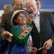 An Andean woman takes a photo of herself with former President Bill Clinton, right, and Mexico's billionaire Carlos Slim during their visit to the San Juan de Lurigancho district of Lima, Peru, Wednesday, Nov. 11, 2015, where the Clinton Foundation runs a program that helps women set up small businesses. Clinton began a tour of Latin America, including El Salvador and Panama, where his foundation also runs programs to aid farmers and women. (AP Photo/Martin Mejia)