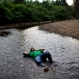 In this Oct. 29, 2015 photo, Daniel Osoriaga, a municipal worker who promotes alternative crops to coca farmers, rests in a shallow area of the Lorencillo River during a four hour trip by boat and foot from Nueva Esperanza to Lorencillo in Peru's Amazon. According to Peru's government, families got financial support or help with alternative crops last year after their coca fields were destroyed. But many get no assistance rejected what was offered. (AP Photo/Rodrigo Abd)