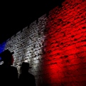 Two Ultra-Orthodox Jews look at Jerusalem's Old City walls illuminated by the colors of the French national flag in solidarity with France after attacks in Paris, in Jerusalem, Sunday, Nov. 15, 2015. (AP Photo/Ariel Schalit)