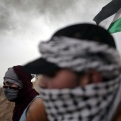 Palestinian protesters cover their faces during clashes with Israeli soldiers on the Israeli border with Gaza in Bureij, in the Gaza Strip, Friday, Nov. 6, 2015. (AP Photo/ Khalil Hamra)