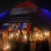 Egyptian tour guides hold a candlelight vigil at the base of the Great Pyramid of Giza in solidarity with victims of attacks in Paris and Beirut and the Russian plane crash in northern Sinai, on the outskirts of Cairo, Sunday, Nov. 15, 2015. (AP Photo/Thomas Hartwell)