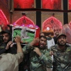 Mourners and militiamen chant slogans against the Islamic State group as they carry one of two flag-draped coffins of members of the Peace Brigades, a Shiite militia group loyal to Shiite cleric Muqtada al-Sadr, during their funeral procession inside the shrine of Imam Ali in Najaf, 100 miles (160 kilometers) south of Baghdad, Saturday, Nov. 7, 2015. The militiamen were killed in Ramadi during fighting with Islamic State militants, their families said. (AP Photo/Anmar Khalil)