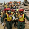 Pakistani rescue workers carry a body of a victim in Lahore, Pakistan, Friday, Nov. 6, 2015. A spokesman for a Pakistani rescue agency says hopes are starting to fade for finding more survivors in the rubble of a four-story factory which collapsed this week, killings dozens of people left many injured. (AP Photo/K.M. Chaudary)