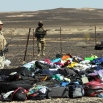 Egyptian Army soldiers stand near luggage and personal effects of passengers a day after a passenger jet bound for St. Petersburg, Russia crashed in Hassana, Egypt, on Sunday, Nov. 1, 2015. (AP Photo)