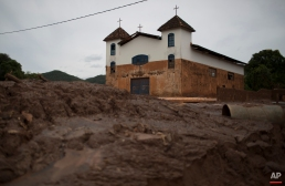 In this Nov. 24, 2015 photo, the color brown on the church's white walls indicate the level which water and mud reached during a recent mudslide triggered by the failing of a dam at a nearby iron ore mine, in Paracatu, Brazil. After the disaster hit, the hamlet of Paracatu and other nearby hamlets like Bento Rodrigues became ghost towns. (AP Photo/Leo Correa)