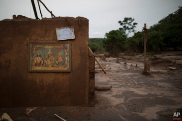 """In this Nov. 24, 2015 photo, a framed military police certificate hangs above a framed image of Jesus Christ and Mary with a message that reads in Portuguese """"Blessing of the homes,"""" hang on the wall of a home destroyed by an early November mudslide, in Paracatu, Brazil. Then the dam at a nearby iron ore mine burst, it unleashed a tsunami of mud that swept away nearly everything in its path, flattening houses, uprooting trees and tossing cars asunder. (AP Photo/Leo Correa)"""