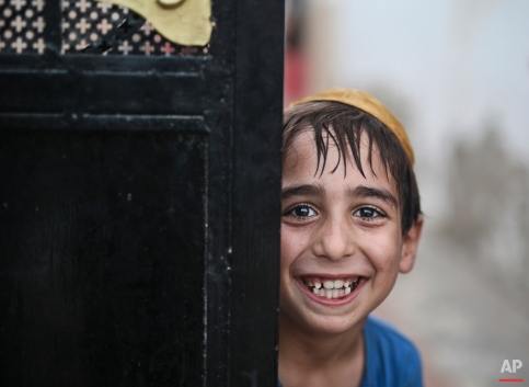 In this Thursday, Oct. 29, 2015 photo, a student covering his head with a Kippah poses for the camera as he leaves the main Talmudic school at Hara Kbira, the main Jewish neighbourhood on the Island of Djerba, southern Tunisia. Tunisia's Jewish population has dwindled from 100,000 in 1956, when the country won independence from France, to less than 1,500, mainly as a result of emigration to France and Israel. But unlike in much of the rest of the Arab world, Tunisian Jews have seen little direct persecution and have only rarely been targeted by extremists. (AP Photo/Mosa'ab Elshamy)