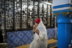 In this Wednesday, Oct. 28, 2015 photo, a Tunisian Jewish woman prays in La Ghriba, the oldest synagogue in Africa, on the Island of Djerba, southern Tunisia. The Jewish community in the resort island of Djerba traces its roots all the way back to Babylonian exile of 586 B.C., and is one of the few communities of its kind to have survived the turmoil around the creation of Israel, when more than 800,000 Jews across the Arab world either emigrated or were driven from their homes. (AP Photo/Mosa'ab Elshamy)