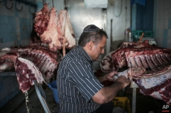 """In this Wednesday, Oct. 28, 2015 photo, Char Haddad, 45, prepares meat in his kosher slaughterhouse at Hara Kbira, the main Jewish neighbourhood on the Island of Djerba, southern Tunisia. The surrounding streets include a kosher butcher, a bakery that sells a traditional tuna-filled pastry known as """"brik"""" and schools that teach lessons in Hebrew, French and Arabic. (AP Photo/Mosa'ab Elshamy)"""