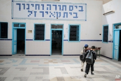 In this Friday, Oct. 30, 2015 photo, boys walk inside a Talmudic school at Hara Kbira, the main Jewish neighbourhood on the Island of Djerba, southern Tunisia. When school lets out, the streets around the ancient synagogue on this Tunisian island fill with rambunctious boys wearing Jewish kippahs and girls in long skirts, shouting to each other in Hebrew, Arabic and French. (AP Photo/Mosa'ab Elshamy)