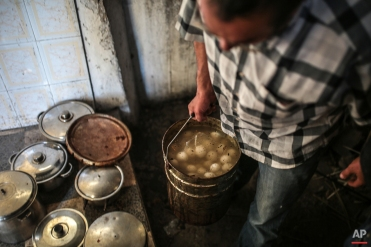In this Friday, Oct. 30, 2015 photo, a man prepares meals for his family on the eve of Shabbath, at Hara Kbira, the main Jewish neighbourhood on the Island of Djerba, southern Tunisia. Tunisia's Jewish population has dwindled from 100,000 in 1956, when the country won independence from France, to less than 1,500, mainly as a result of emigration to France and Israel. But unlike in much of the rest of the Arab world, Tunisian Jews have seen little direct persecution and have only rarely been targeted by extremists. (AP Photo/Mosa'ab Elshamy)