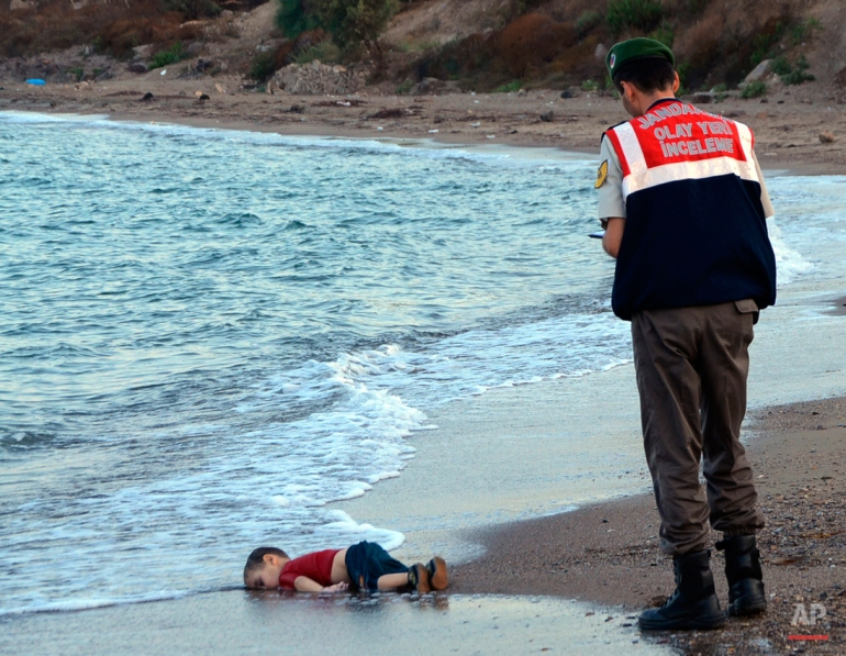 A paramilitary police officer investigates the scene before carrying the lifeless body of 3-year-old Aylan Kurdi from the sea shore, near the beach resort of Bodrum, Turkey, early Wednesday, Sept. 2, 2015. A number of migrants are known to have died and some are still reported missing, after boats carrying them to the Greek island of Kos capsized. (AP Photo/DHA)