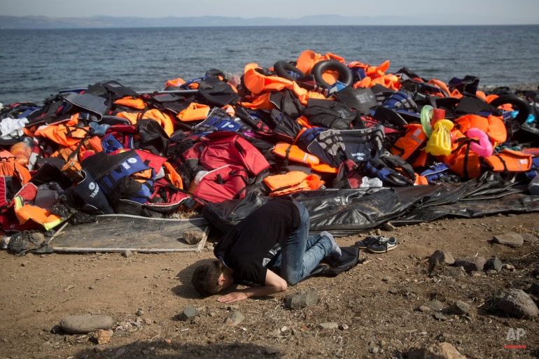 An Afghan migrant prays in front a huge pile of life vests after arriving with others from Turkey to the shores of the Greek island of Lesbos, on an inflatable dinghy, Saturday Sept. 26, 2015. More than 260,000 asylum-seekers have arrived in Greece so far this year, most reaching the country's eastern islands on flimsy rafts or boats from the nearby Turkish coast. (AP Photo/Petros Giannakouris)