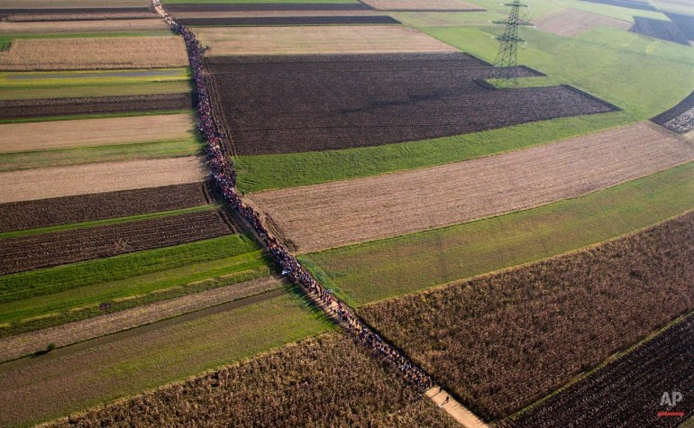 A column of migrants moves through fields after crossing from Croatia, in Rigonce, Slovenia, Sunday, Oct. 25, 2015. Thousands of people are trying to reach central and northern Europe via the Balkans, but often have to wait for days in mud and rain at the Serbian, Croatian and Slovenian borders. (AP Photo/Darko Bandic)