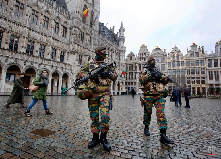 Police officers patrol the Grand Place in central Brussels, Belgium, Tuesday, Nov. 24, 2015. The lockdown has closed the capital's subways and schools. Officials have recommended that popular shopping districts be shuttered and advised people to avoid public places since they could be targeted by terrorists. (AP Photo/Michael Probst)