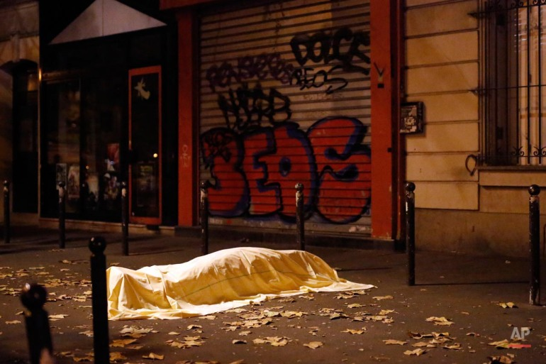 A victim of a terrorist attack lies dead outside the Bataclan theater in Paris, Nov. 13, 2015.  (AP Photo/Jerome Delay)
