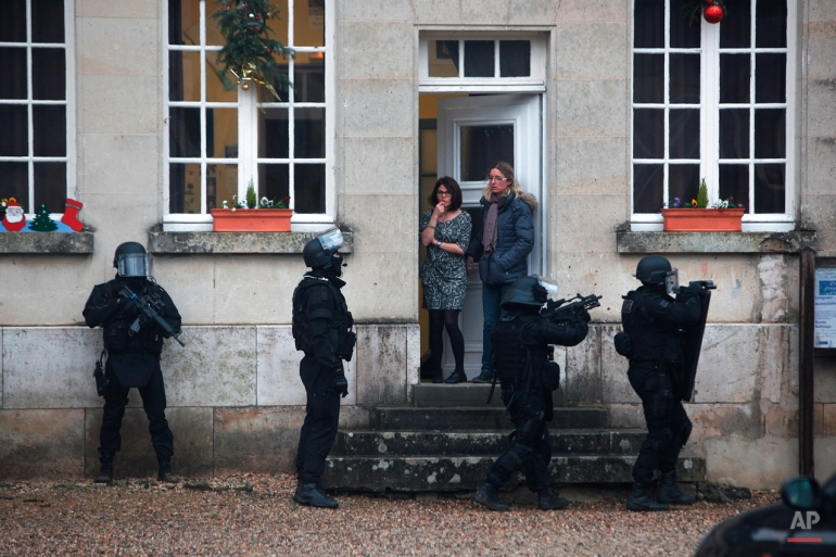 French riot officers patrol in Longpont, north of Paris, Thursday, Jan. 8, 2015. Scattered gunfire and explosions shook the city as its frightened yet defiant citizens held a day of mourning for 12 people slain at the Paris newspaper Charlie Hebdo. French police hunted down the two heavily armed brothers suspected in the massacre. (AP Photo/Thibault Camus)