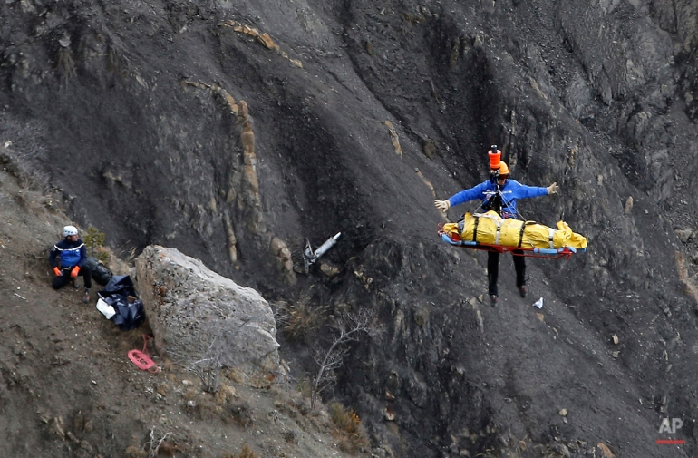 A rescue worker is lifted into an helicopter at the crash site near Seyne-les-Alpes, France, Thursday, March 26, 2015. The co-pilot of a Germanwings jet barricaded himself in the cockpit and rammed the plane full speed into the French Alps, ignoring the captain's frantic pounding on the cockpit door and the screams of terror from passengers. In a split second, he killed all 150 people aboard the plane. (AP Photo/Laurent Cipriani)