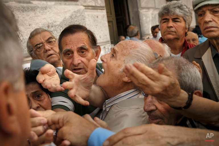 Pensioners try to get a number to enter inside a bank in Athens, Wednesday, July 1, 2015. About 1,000 bank branches around the country were ordered by the government to reopen to help desperate pensioners without ATM cards cash up to 120 euros ($134) from their retirement checks.  (AP Photo/Daniel Ochoa de Olza)