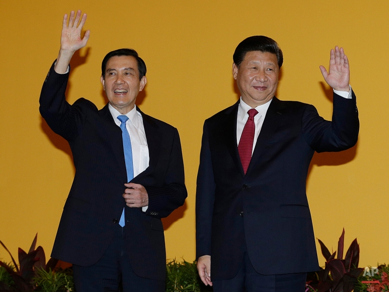 Taiwanese President Ma Ying-jeou, left, and Chinese President Xi Jinping, right, wave to the media at the Shangri-la Hotel on Saturday, Nov. 7, 2015, in Singapore. The two leaders shook hands at the start of a historic meeting, marking the first top level contact between the formerly bitter Cold War foes since they split amid civil war 66 years ago. (AP Photo/Wong Maye-E)