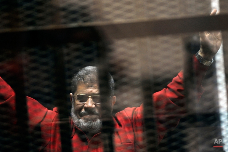 Ousted Egyptian President Mohammed Morsi, wearing a red jumpsuit that designates he has been sentenced to death, raises his hands inside a defendants cage in a makeshift courtroom at the national police academy, in an eastern suburb of Cairo, Egypt, Sunday, June 21, 2015. The week before, a court sentenced Morsi to death in a separate case over a prison break in 2011. (AP Photo/Ahmed Omar)