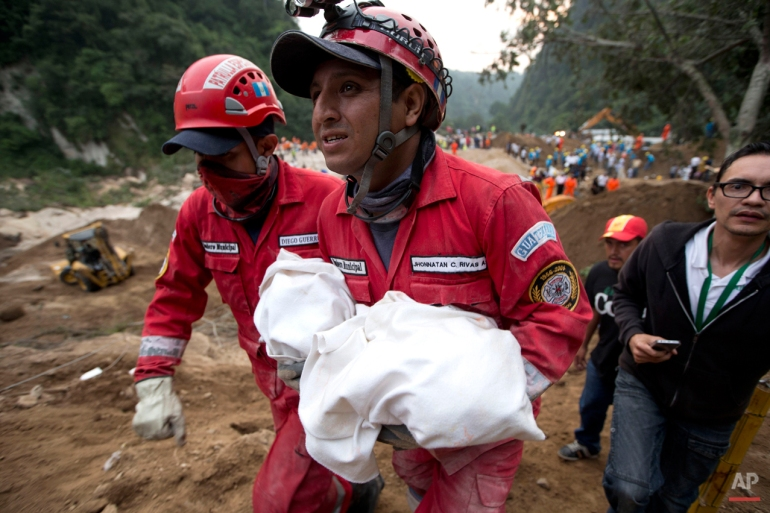 A fireman carries the body of a child recovered from the site of a landslide in Cambray, a neighborhood in the suburb of Santa Catarina Pinula, about 10 miles east of Guatemala City, Friday, Oct. 2, 2015. The hill that towers over Cambray collapsed after heavy rains, burying several houses with dirt, mud and rocks.  (AP Photo/Moises Castillo)