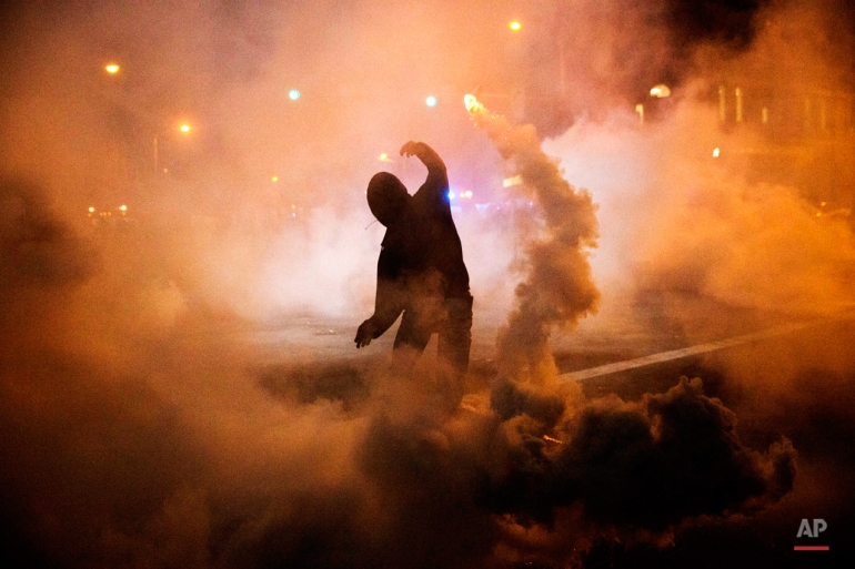 A protester throws a tear gas canister back toward riot police after a 10 p.m. curfew went into effect in the wake of Monday's riots following the funeral for Freddie Gray, Tuesday, April 28, 2015, in Baltimore. Gray suffered a spinal injury in police custody and later died. (AP Photo/David Goldman)
