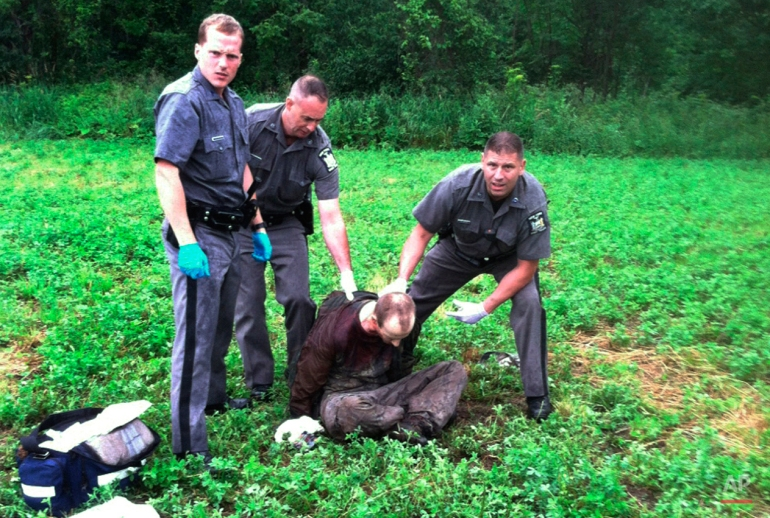 Police stand over David Sweat after he was shot and captured near the Canadian border Sunday, June 28, 2015, in Constable, N.Y. Sweat is the second of two convicted murderers who staged a brazen escape from a maximum-security prison in northern New York. His capture came two days after his escape partner, Richard Matt, was shot and killed by authorities. (AP Photo)