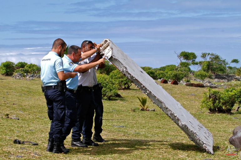 French police officers inspect a piece of debris from a plane in Saint-Andre, Reunion Island on July 29, 2015. It was later confirmed the wing flap found on an island in the western Indian Ocean was part of Malaysia Airlines Flight 370, a Boeing 777 that had disappeared 17 months ago.  (AP Photo/Lucas Marie)