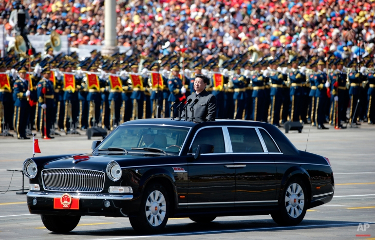 Chinese President Xi Jinping stands in a car to review the army during a parade commemorating the 70th anniversary of Japan's surrender during World War II held in front of Tiananmen Gate in Beijing, Sept. 3, 2015. The spectacle involved more than 12,000 troops, 500 pieces of military hardware and 200 aircraft of various types, representing what military officials say is the Chinese military's most cutting-edge technology. (AP Photo/Ng Han Guan)