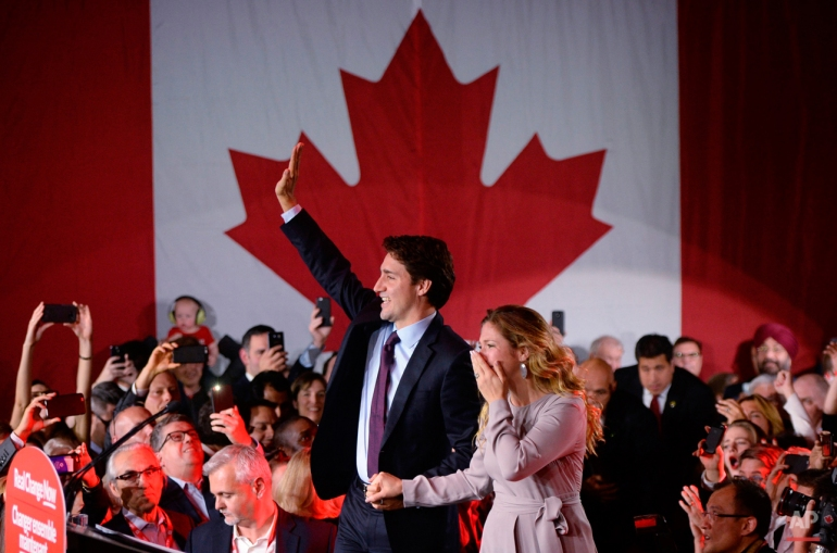 Liberal leader Justin Trudeau waves to supporters with his wife, Sophie Gregoire, at the Liberal party headquarters in Montreal, Tuesday, Oct. 20, 2015. Trudeau, the son of late Prime Minister Pierre Trudeau, became Canada's new prime minister after beating Conservative Stephen Harper. (Sean Kilpatrick/The Canadian Press via AP)