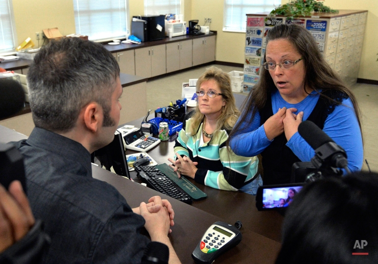Rowan County Clerk Kim Davis, right, talks with David Moore following her office's refusal to issue marriage licenses at the Rowan County Courthouse in Morehead, Ky., Tuesday, Sept. 1, 2015. Although her appeal to the U.S. Supreme Court was denied, Davis still refused to issue marriage licenses. (AP Photo/Timothy D. Easley)