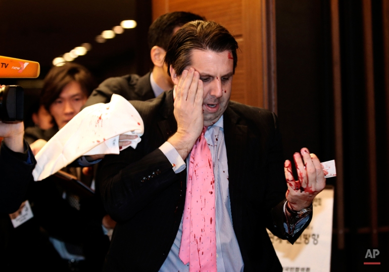 U.S. Ambassador to South Korea Mark Lippert leaves a lecture hall for a hospital in Seoul, South Korea, Thursday, March 5, 2015 after being attacked by a man. Lippert was attacked by a man wielding a razor and screaming that the rival Koreas should be unified. (AP Photo/Yonhap, Kim Ju-Sung)