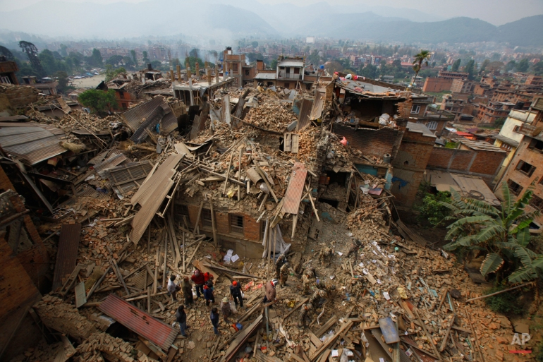 Rescue workers remove debris as they search for victims of earthquake in Bhaktapur near Kathmandu, Nepal, Sunday, April 26, 2015. A strong  earthquake shook Nepal's capital and the densely populated Kathmandu Valley before noon, causing extensive damage with toppled walls and collapsed buildings. (AP Photo/Niranjan Shrestha)