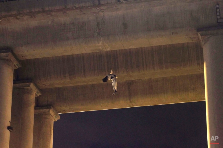 The body of an unidentified man hangs from his waist under an overpass in the southern part of Mexico City, early Monday, Oct. 19, 2015. The man was found wrapped in white bandages and a hood was covering his head. This is the first time a body appeared on a bridge or overpass in Mexico City, a common practice among criminal gangs fighting for control of turf in other regions of Mexico. (AP Photo/Jair Cabrera)
