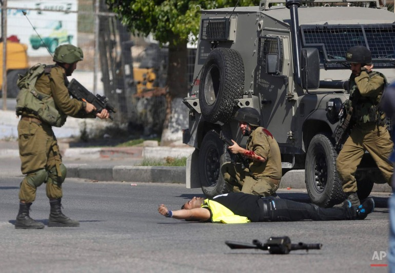 "An Israeli soldier shoots a Palestinian holding a knife after he stabbed another Israeli soldier, seen kneeling, during clashes in Hebron, West Bank, Friday, Oct. 16, 2015. The Palestinian man wearing a yellow ""press"" vest and a T-shirt identifying him as journalist stabbed and wounded the soldier in the latest in a monthlong spate of attacks. (AP Photo/Nasser Shiyoukhi)"