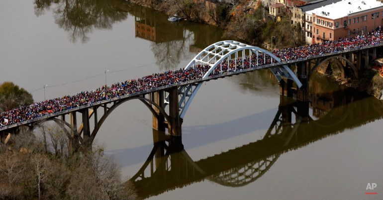 "A large crowds moves in a symbolic walk across the Edmund Pettus Bridge, Sunday, March 8, 2015, in Selma, Ala., to mark the 50th anniversary of ""Bloody Sunday,"" a civil rights march in which protestors were beaten, trampled and tear-gassed by police at the bridge. (AP Photo/Butch Dill)"