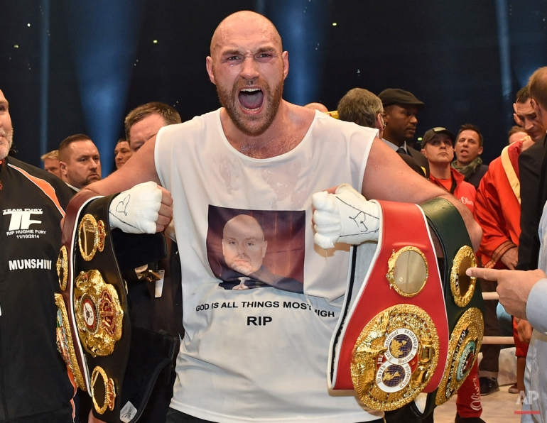 Britain's new world boxing champion Tyson Fury celebrates with the WBA, IBF, WBO and  IBO belts after winning the world heavyweight title fight against Ukraine's Wladimir Klitschko in the Esprit Arena in Duesseldorf, western Germany, Sunday, Nov. 29, 2015. (AP Photo/Martin Meissner)