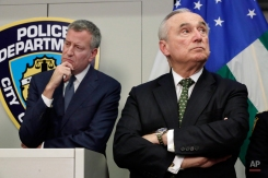 New York Mayor Bill deBlasio, left, and New York City Police Commissioner William Bratton, listen as crime statistics are presented during a news conference at police headquarters, in New York, Monday, Jan. 4, 2016. Arrests were down more than 56,000 in the past two years, according to preliminary annual statistics released Monday. (AP Photo/Richard Drew)