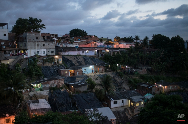 In this Jan. 27, 2016 photo, homes are lit by the setting sun in Ibura, one of the neighborhoods with the highest numbers of suspected cases of children born with microcephaly in Recife, Pernambuco state, Brazil. The Zika virus is the suspected culprit of 3,400 cases of microcephaly in the country. (AP Photo/Felipe Dana)