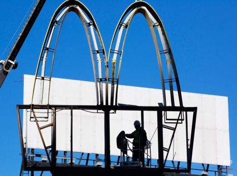 """A sign company worker dismantles the """"Golden Arches"""" of a McDonald's restaurant, Monday, Jan. 4, 2016, in New York. The fast food chain restaurant at the corner of 34th Street and Tenth Avenue in New York is being torn down to make way for a skyscraper, part of the Hudson Yards development on Manhattan's west side. (AP Photo/Mark Lennihan)"""