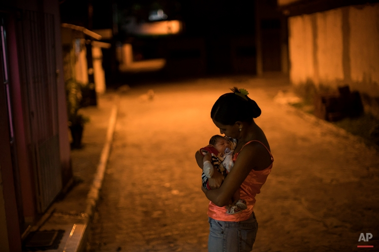 In this Jan. 26, 2016 photo, Daniele Ferreira dos Santos holds her son Juan Pedro, who was born with microcephaly, outside her house in Recife, Pernambuco state, Brazil. Santos was never diagnosed with Zika, but she blames the virus for her son's defect and for the terrible toll it has taken on her life. (AP Photo/Felipe Dana)