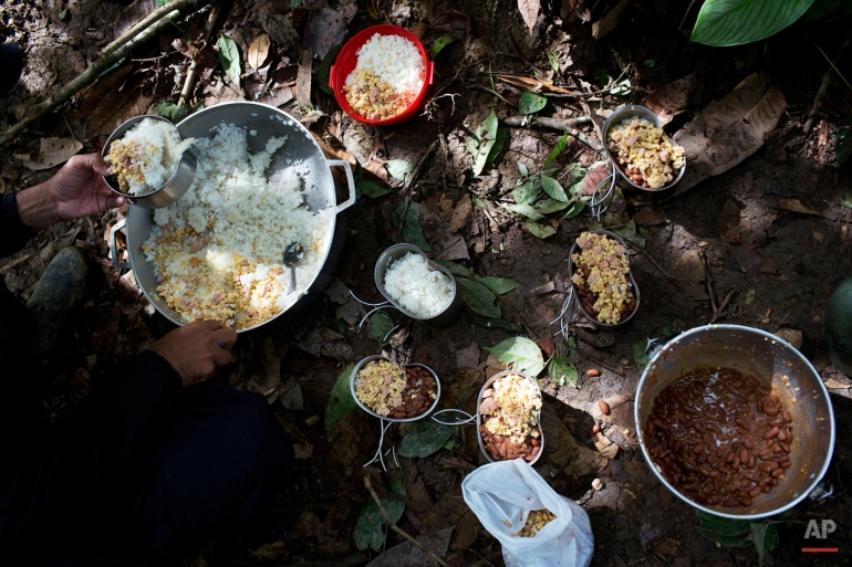 "In this Jan. 4, 2016 photo, a rebel soldier of the 36th Front of the Revolutionary Armed Forces of Colombia, or FARC, serves up a portion of rice, eggs, sausage and beans, for breakfast, at a hidden camp in Antioquia state, in the northwest Andes of Colombia. If the FARC seems at times stuck in a time warp, rebels share an enormous gratitude to the insurgency for rescuing them from poverty, providing them with a ""family"" and sense of belonging. (AP Photo/Rodrigo Abd)"