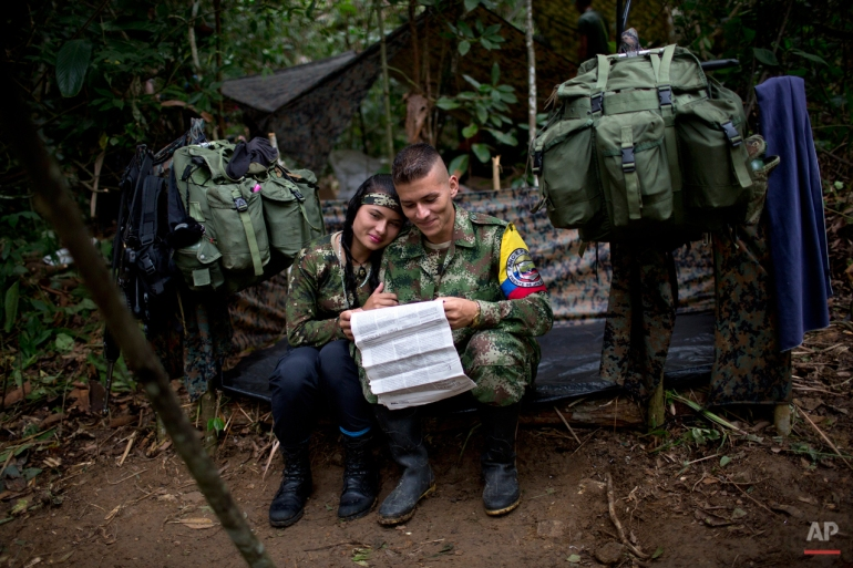 "In this Jan. 4, 2016 photo, Juliana, a rebel soldier of the 36th Front of the Revolutionary Armed Forces of Colombia, or FARC, sits with her boyfriend Alexis, in their makeshift tent, inside their hidden camp in Antioquia, Colombia. ""Inside the guerrilla we don't touch money, everything is given to us, from medicine to cigarettes. That's why there's no dependency in which she expects me to provide for her as is common in Latin America,"" explains Alexis. ""Between us there's just love.' (AP Photo/Rodrigo Abd)"