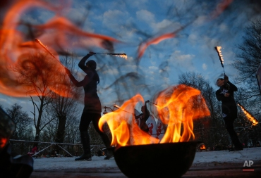 Fire show actors perform during a fire and smoke festival as they celebrate incoming Orthodox Christmas in St. Petersburg, Russia, Monday, Jan. 4, 2016. Russians continue to celebrate the New Year and Orthodox Christmas from Jan. 1 to Jan. 10. (AP Photo/Dmitry Lovetsky)