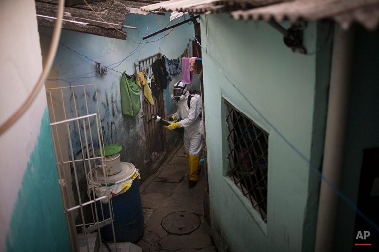 In this Jan. 26, 2016 photo, a municipal worker sprays insecticide to combat the Aedes aegypti mosquitoes that transmits the Zika virus, at the Imbiribeira neighborhood in Recife, Pernambuco state, Brazil. In the face of the spiraling public health crisis, President Dilma Rousseff has declared war on Aedes, with the government promising to deploy some 220,000 members of the Armed Forces to go door-to-door to help educate the population about how to prevent the mosquito's spread. (AP Photo/Felipe Dana)